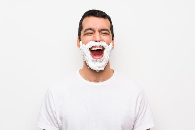 Mann seinen bart rasieren über isolierte weiße wand mit weit offenem mund nach vorne schreien Premium Fotos