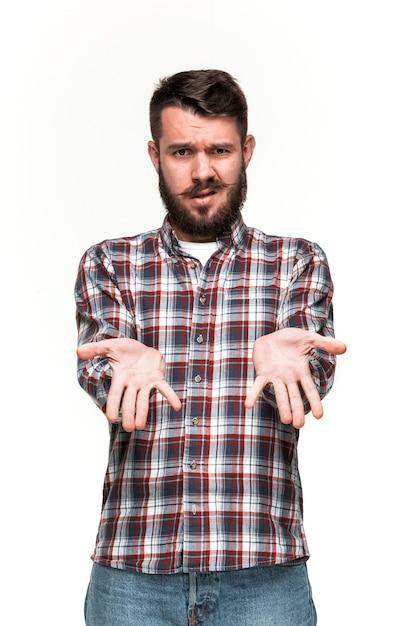 Mann sieht schmollmund aus. über weißer wand Kostenlose Fotos