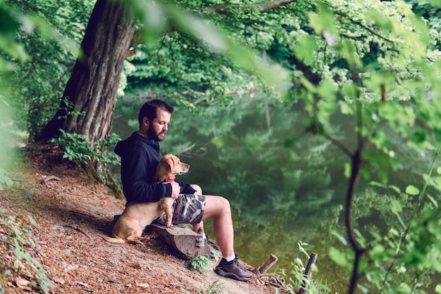 Mann sitzt auf der bank mit dem hund am see Premium Fotos