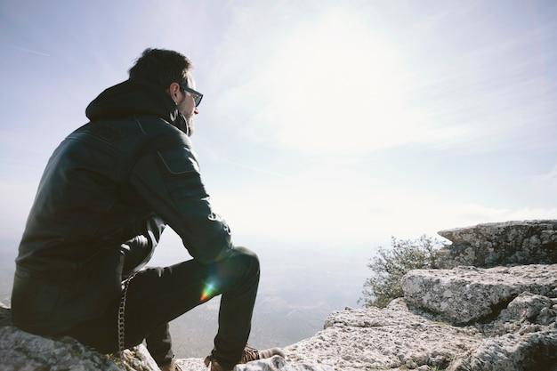 Mann sitzt auf einem felsen Kostenlose Fotos