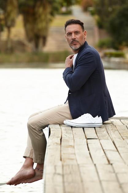 Mann sitzt auf einem steg posiert Kostenlose Fotos