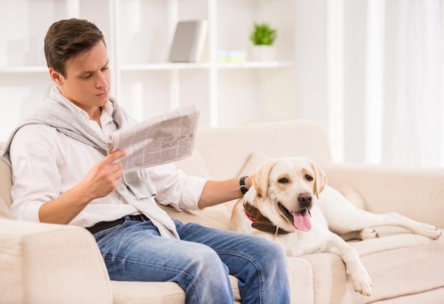 Mann sitzt auf sofa mit hund und liest eine zeitung. Premium Fotos