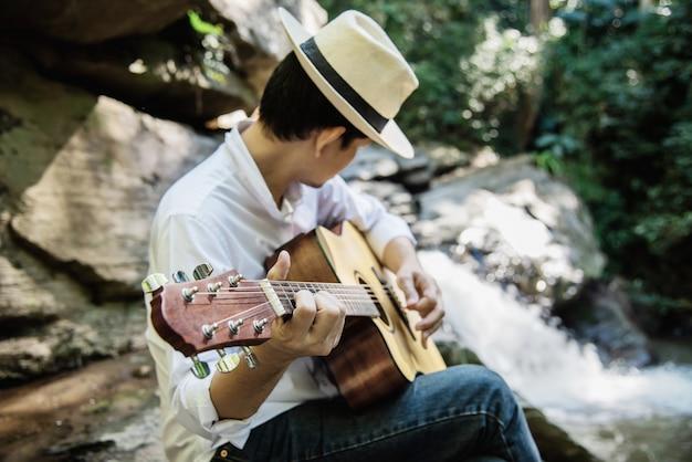 Mann spielen gitarre in der nähe des wasserfalls Kostenlose Fotos