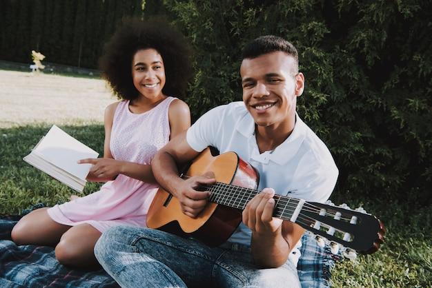 Mann spielt auf gitarre zu seinem mädchen frau liest buch Premium Fotos