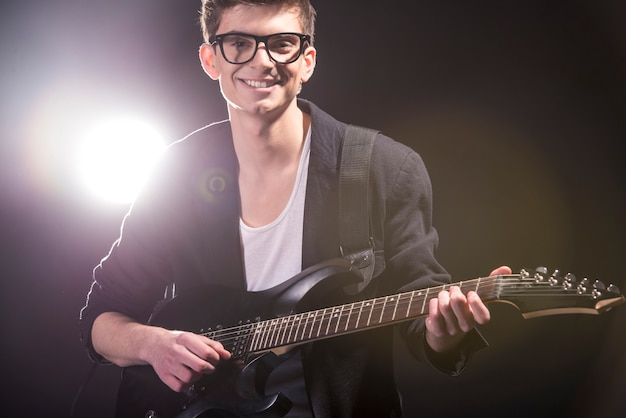 Mann spielt gitarre im dunklen raum mit lichtern hinter ihm. Premium Fotos