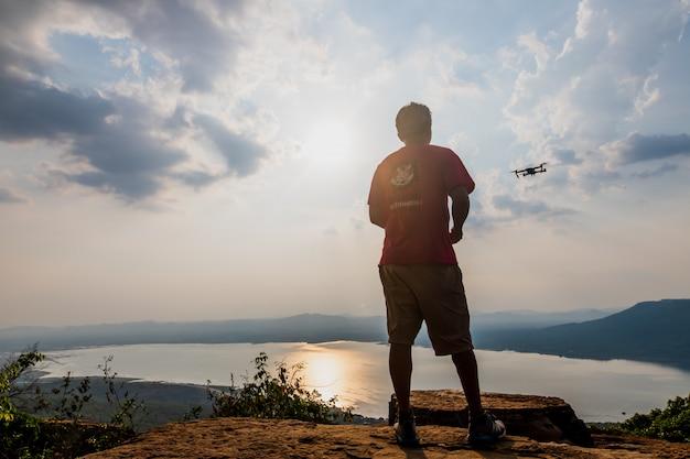 Mann spielt mit der drohne. silhouette gegen den sonnenuntergang himmel Premium Fotos
