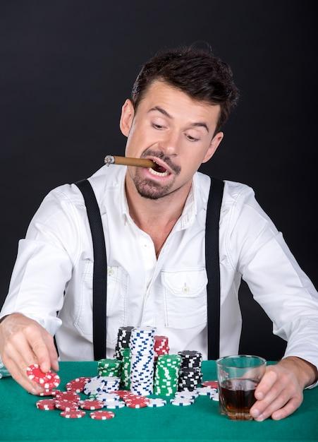 Mann spielt poker mit zigarre und einem glas whisky. Premium Fotos