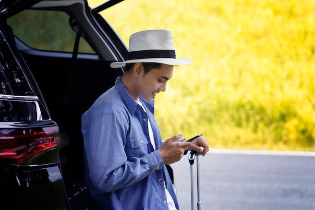 Mann stand mit handy und gepäck im auto Premium Fotos