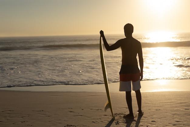 Mann stehend mit surfbrett am strand Kostenlose Fotos