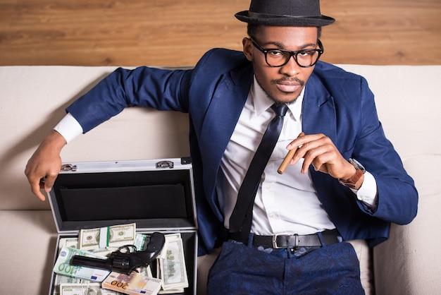 Mann trägt anzug und hut mit pistole und geld. Premium Fotos