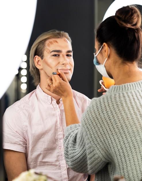 Mann trägt make-up und frau macht seine kontur Kostenlose Fotos