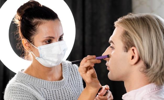 Mann trägt make-up und frau trägt maske Kostenlose Fotos