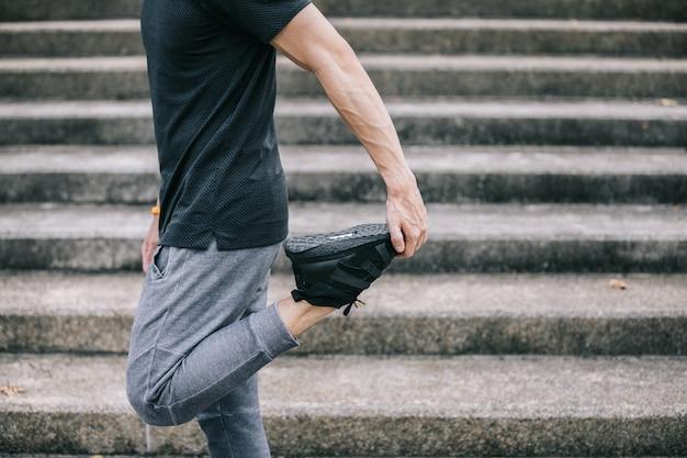 Mann trainieren, beine für das aufwärmen ausdehnend, bevor sie treppen trainieren und klettern. Premium Fotos