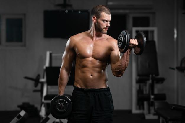 Mann trainiert im fitnessstudio. sportlicher mann trainiert mit hanteln und pumpt seinen bizeps Premium Fotos