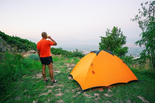 Mann trinkt aus der tasse nahe einem orangefarbenen zelt, das auf hügel steht Premium Fotos
