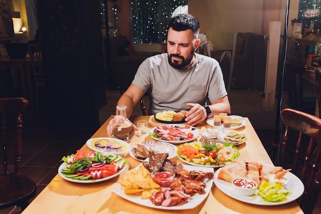 Mann trinkt wodka an einem großen tisch mit essen und snacks. Premium Fotos