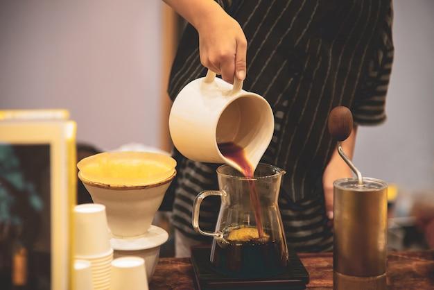 Mann tropft heißen kaffeespezialitäten am morgen im café. Premium Fotos