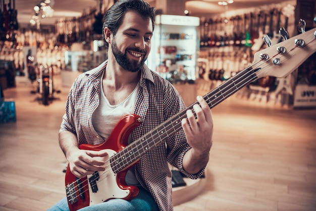 Mann überprüft e-gitarre, bevor er im musikgeschäft kauft Premium Fotos