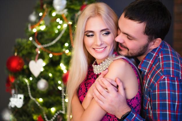 Mann umarmt seine schöne junge frau über die schultern während der neujahrsferien zu hause Premium Fotos