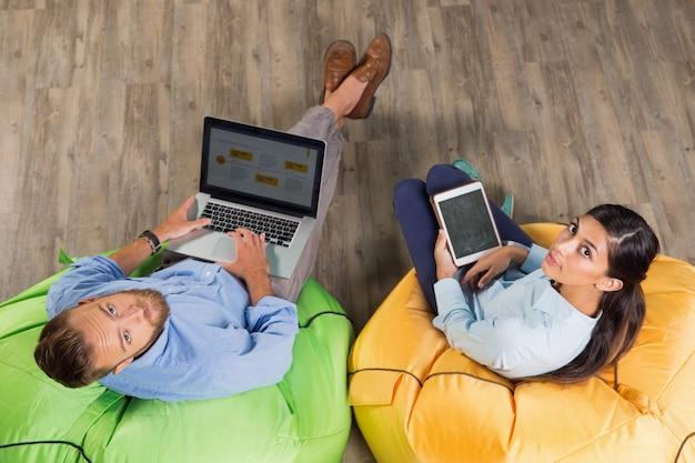 Mann und frau arbeiten auf hellem sitzsäcke Kostenlose Fotos