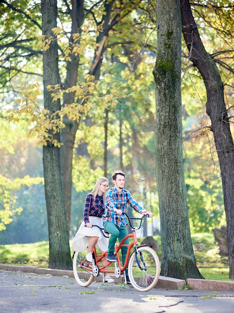 Mann und frau auf tandemfahrrad im park Premium Fotos
