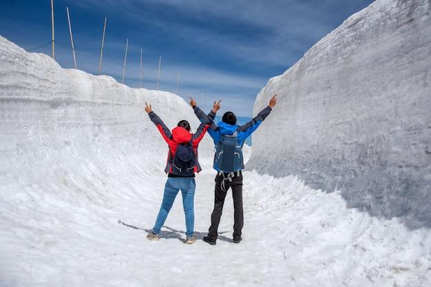 Mann und frau breiteten hand auf schneegehweg bei tateyama kurobe alpine route aus. Premium Fotos