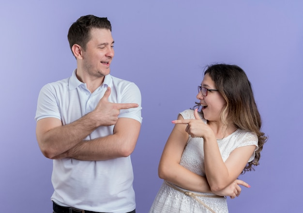 Mann und frau des jungen paares, die auf einander mit den lächelnden zeigefingern zeigen, die über der blauen wand stehen Kostenlose Fotos