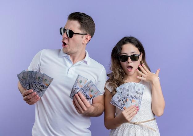 Mann und frau des jungen paares, die bargeld glücklich und aufgeregt über der blauen wand stehen Kostenlose Fotos