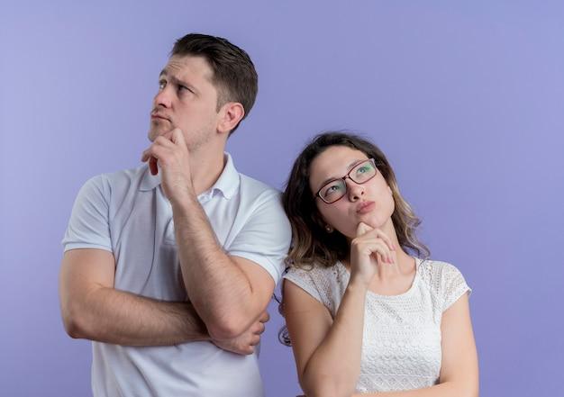 Mann und frau des jungen paares, die beiseite mit nachdenklichem ausdruck auf gesicht stehen, das über blauer wand steht Kostenlose Fotos
