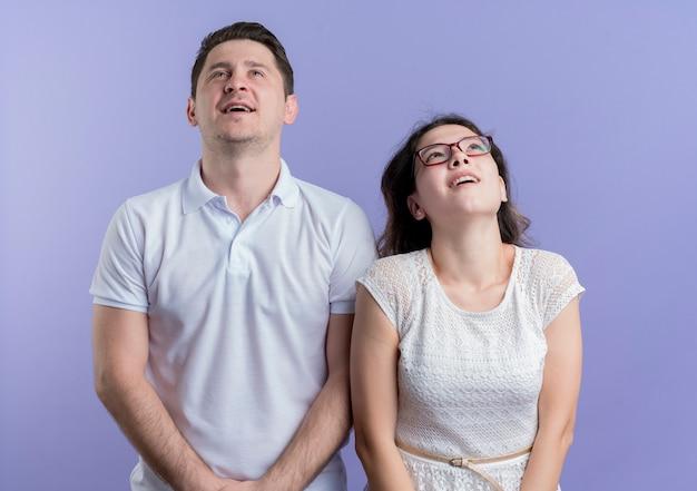 Mann und frau des jungen paares, die lächelnd und denkend über der blauen wand stehend suchen Kostenlose Fotos