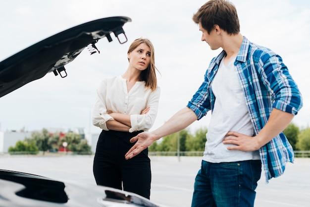 Mann und frau, die automotor überprüfen Kostenlose Fotos