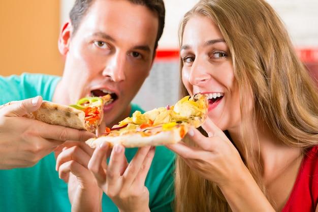 Mann und frau, die eine pizza essen Premium Fotos