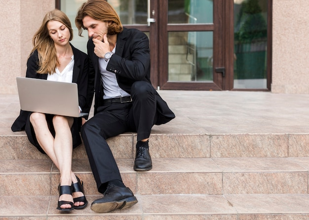 Mann und frau, die einen laptop auf treppen verwenden Kostenlose Fotos