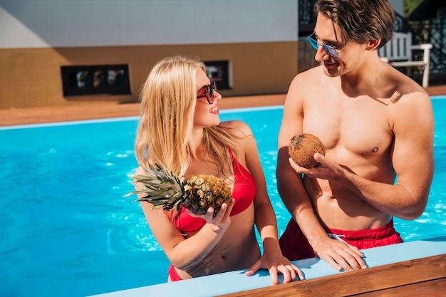 Mann und frau, die früchte im pool halten Kostenlose Fotos