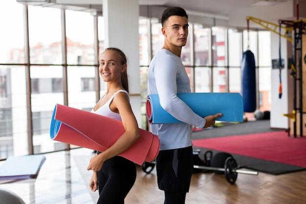 Mann und frau, die yogamatten halten Kostenlose Fotos
