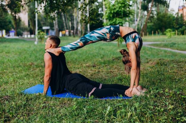 Mann und frau, die zusammen yoga im park im freien tun. mann, der eine frau küsst Premium Fotos
