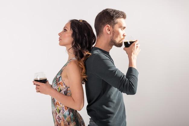 Mann und frau halten gläser dunkles bier an weißer wand mit kopierraum. oktoberfest-konzept. Premium Fotos