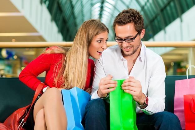 Mann und frau im einkaufszentrum mit taschen Premium Fotos