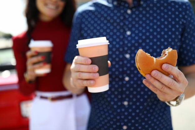 Mann und frau im hintergrund halten kaffee und hamburger Premium Fotos