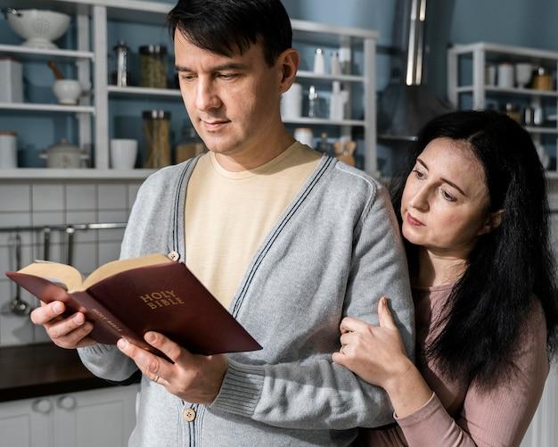 Mann und frau in der küche lesen aus der bibel Kostenlose Fotos