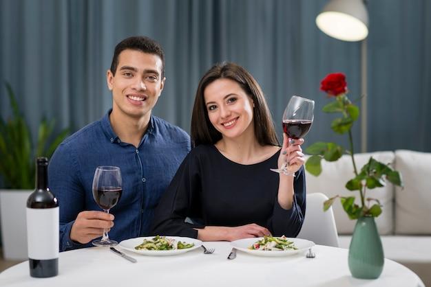 Mann und frau jubeln bei ihrem romantischen abendessen Kostenlose Fotos