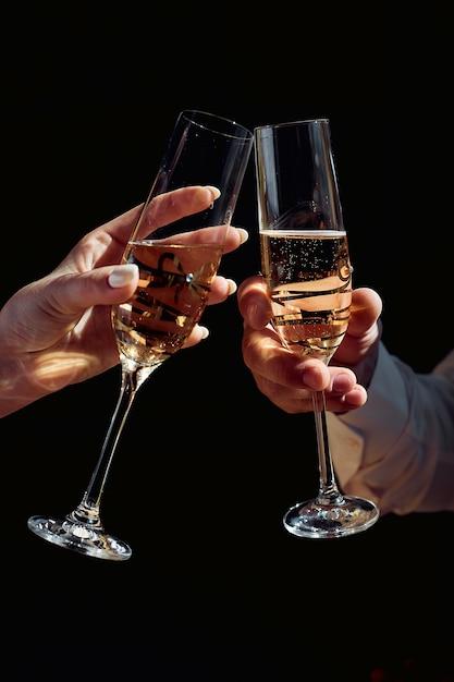 Mann und frau kinn kinn mit sektgläsern, weibliche und männliche hand hält ein glas mit champagner auf dunkel Premium Fotos