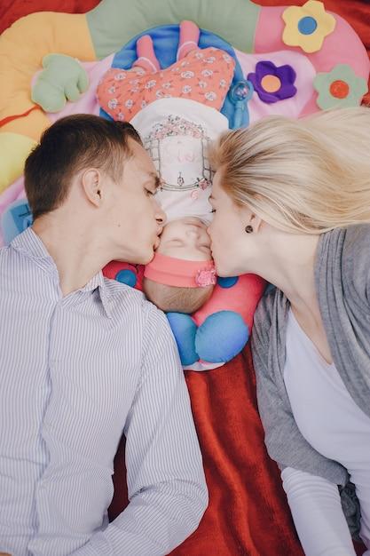 Mann und frau küssen ihr baby   Kostenlose Foto