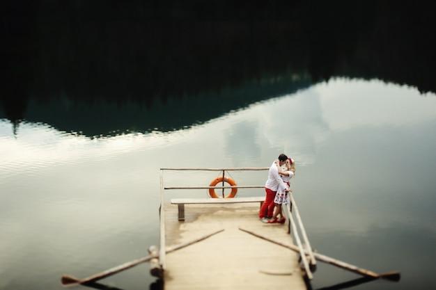 Veranda Holz mann und frau kuss stehen auf holz veranda über bergsee