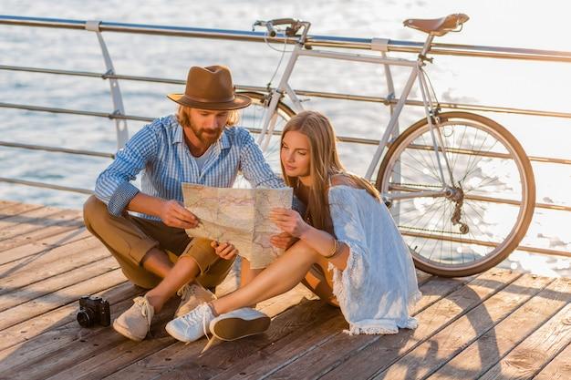 Mann und frau mit blondem haar boho hipster-stil mode, die spaß zusammen haben, in der karte sightseeing suchen Kostenlose Fotos