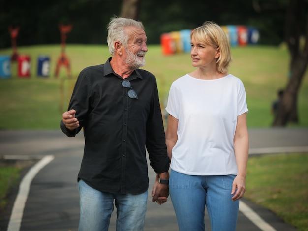 Mann und frau mit zwei glücklichen senioren gehen und sprechen im park Premium Fotos