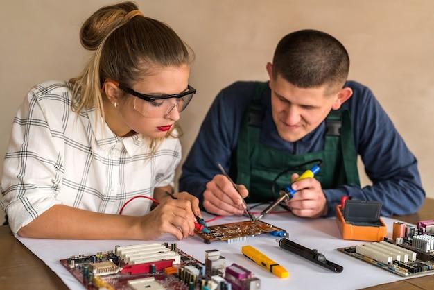 Mann und frau reparieren computer motherboard in werkstatt Premium Fotos