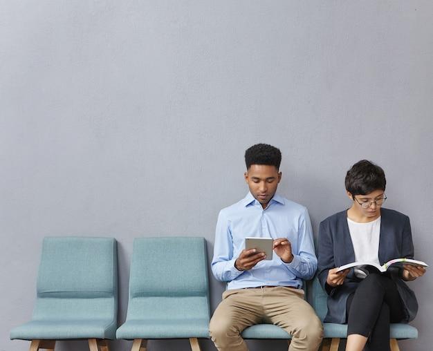 Mann und frau sitzen im wartezimmer Kostenlose Fotos
