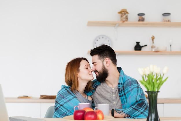 Mann und frau sitzen in der küche mit einer decke Kostenlose Fotos