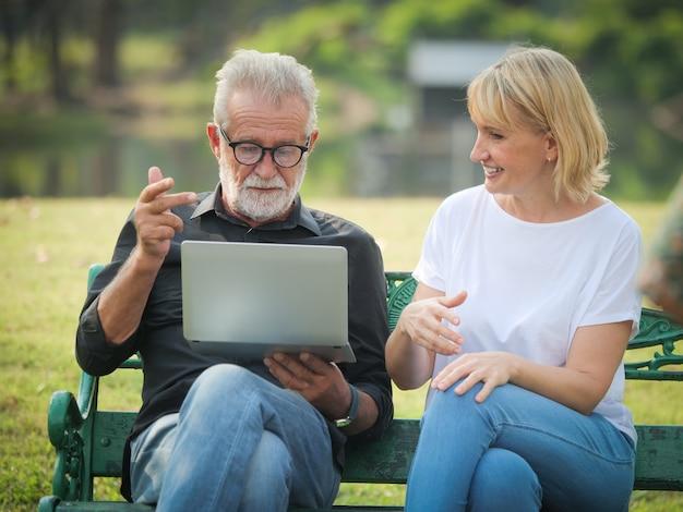 Mann und frau sitzen und benutzen computerlaptop im park Premium Fotos